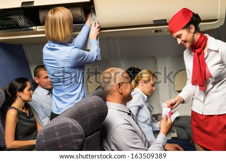 Air stewardess check passenger ticket in airplane cabin smiling