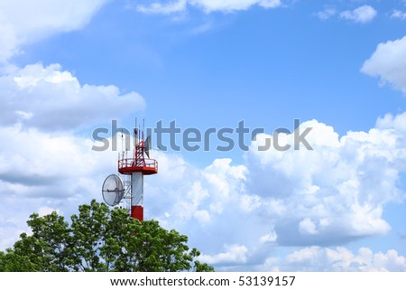 Air traffic control communications tower against cloudy blue sky, symbolic background