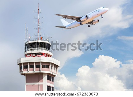 Air traffic control tower in international airport with passenger airplane jet taking off in the background
