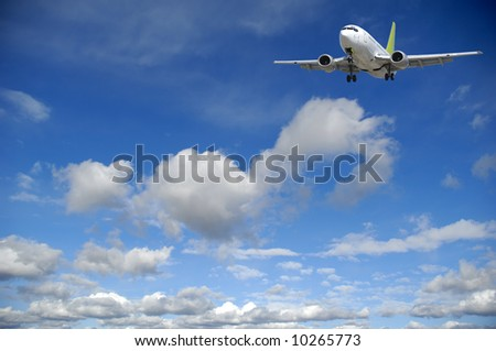 Air travel - Plane flying in blue and cloudy sky. - stock photo