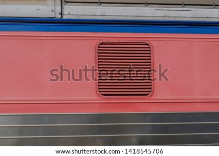 Air vent grate on side of red train car on sunny day.   #1418545706