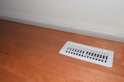 Air vent with with white cover on a hardwood floor