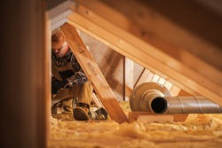 Air Ventilation Installer Working in Attic. Air Quality Heating and Cooling System Building by Professional Technician.