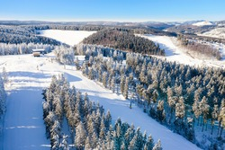 Air view on the winter sports slopes at the ski lift carousel Winterberg. Sledding slope and ski slopes between snow covered spruce forests.