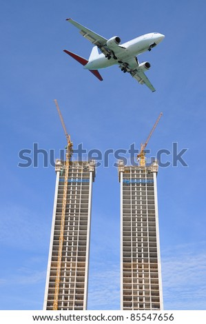 Airborne Airplane Flying in Blue Sky Above Two Skyline High Buildings under Construction