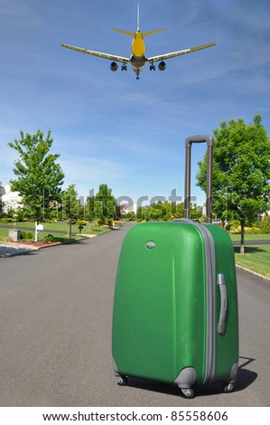 Airborne Airplane flying over Green Luggage on Suburban Residential Neighborhood Street Sunny Day