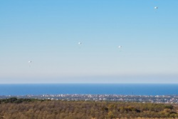 Airborne troops a mass parachute drop over the sea. On a blue sky background