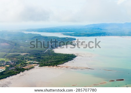 Airborne view of developed lands along the shallow, brown, silty waters of an estuary and wet lands under a cloudy, overcast sky.