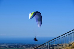 Aircraft, a parachute with a motor. Man with para glider fly in the blue sky.