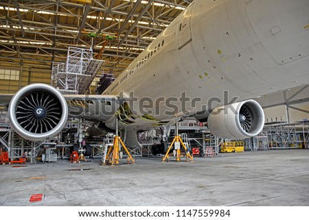 Aircraft (airplane) lift up from the floor by aircraft jack for maintenance at aircraft hangar.Aircraft on jack in hangar for maintenance service check by mechanic.
