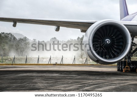 Aircraft (airplane) running jet engine after maintenance. Jet engine blowing dust in the wind while engine running.