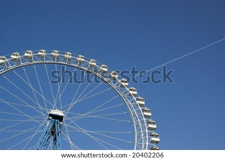 Aircraft and ferris wheel on sky background