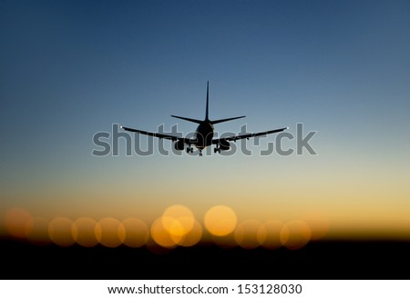 aircraft approaching airport at blue and orange sunset