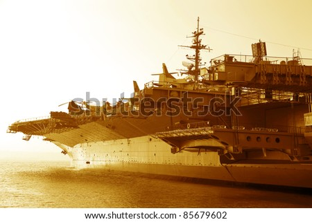 Aircraft carrier in the ocean at sunset