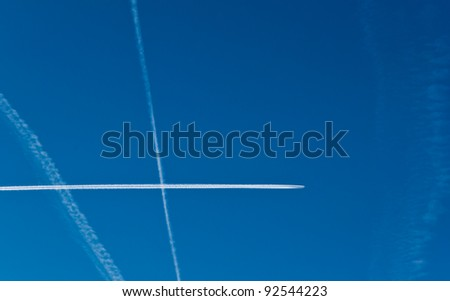 Aircraft contrails against the blue sky on a clear winter day in the Netherlands.