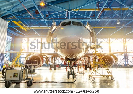 Aircraft in the aviation industrial hangar on maintenance, outside the gate bright light