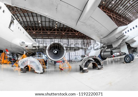 Aircraft in the hangar repair and maintenance, view from under the wing of the airplane