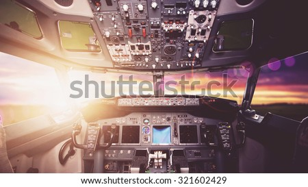 Aircraft interior, cockpit view inside the airliner. Point of view from a pilot place in a plane. Sunny sky horizon view from an airplane front glass.