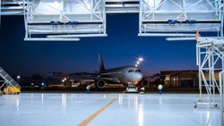 Aircraft Maintenance Hangar Where New Airplane is Toed by a Pushback Tractor/ Tug onto Landing Strip. Crew of Mechanics, Engineers and Drivers Works Busily.