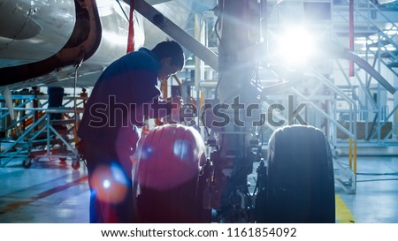 Aircraft maintenance mechanic with a flash light inspects plane chassis in a hangar.