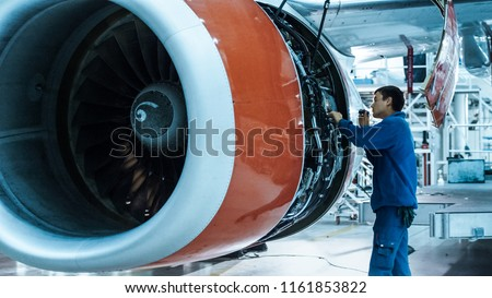 Aircraft maintenance mechanic with a flash light inspects plane engine in a hangar.