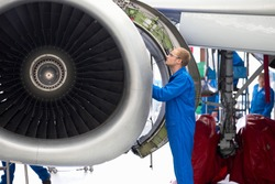 Aircraft maintenance technician checking airplane engine for safety in the airport hangar