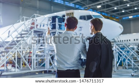 Aircraft Maintenance Worker and Engineer Having Conversation. Looking at the airplane.