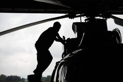 Aircraft mechanic, black and white  ,  Male pilot checks the tail of helicopter before the flight. Mechanic checking helicopter before take off.