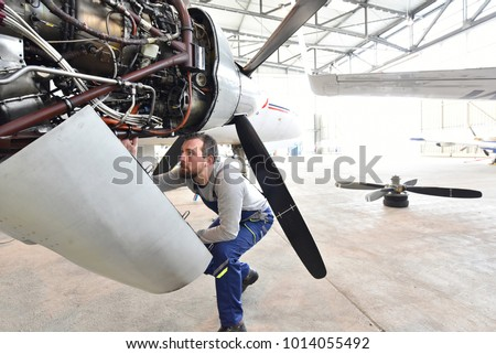 Aircraft mechanic repairs an aircraft engine in an airport hangar