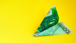aircraft, One hundred euro plane isolated on yellow background, copy space for text, euro plane, travel and money