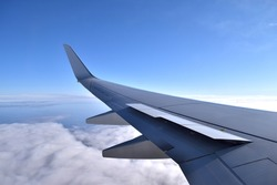 Aircraft spoilers lifting before landing. Aerial view of airplane wing with blue sky and clouds. Preparation for landing.