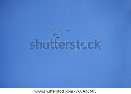 Aircraft squadron flying around the moon in triangle formation