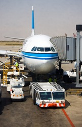Aircraft tow tractor standing by for push back.