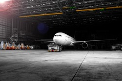 Aircraft towing tractors towing aircraft (airplane) out from aircraft hangar after finished maintenance.