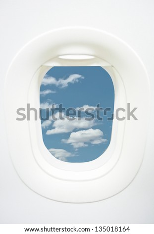 Aircraft Window with plane cruising against bright blue sky