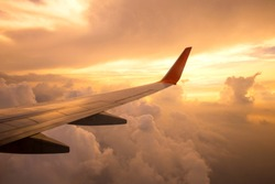 Aircraft wing on the clouds of sunset ,flying traveling background