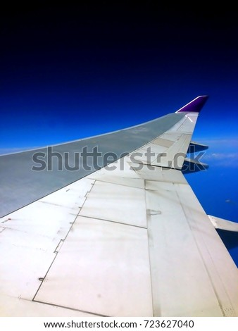 Aircraft wing with a blue sky view from the windows of airplane. #723627040