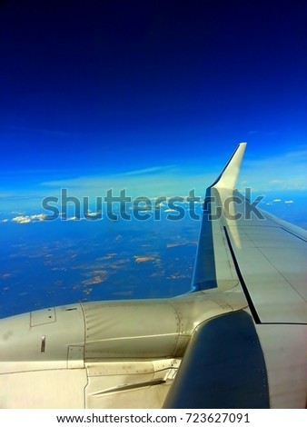 Aircraft wing with a blue sky view from the windows of airplane. #723627091