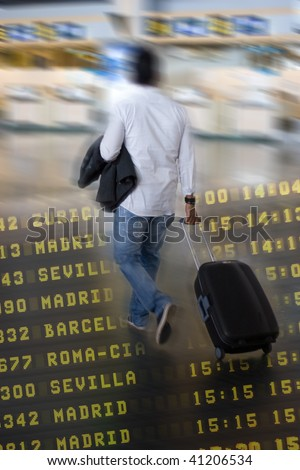 Airline Passenger at the Airport pulling his suitcase