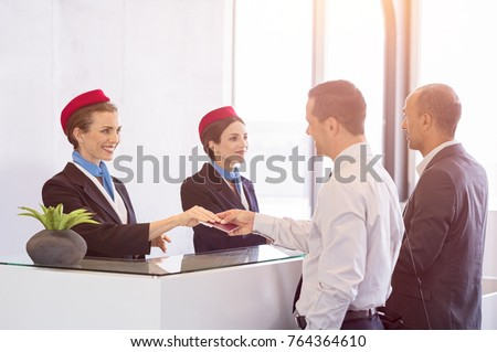 Airline passengers checking in at airline counter. Young woman giving passport and ticket back to businessman at airport check in. Two businessmen at airport checkin desk leaving on business trip.