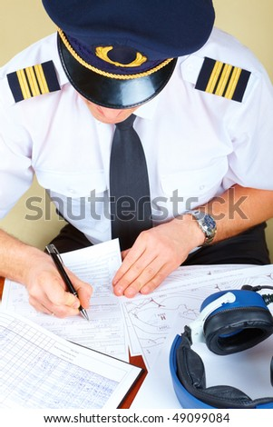 Airline pilot wearing hat, shirt with epaulets and tie filling in and checking papers flight plan, log book and weather forecast. Headset on the table.