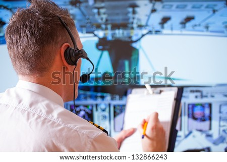 Airline pilot wearing uniform with epauletes and headset, writting on notepad inside airliner