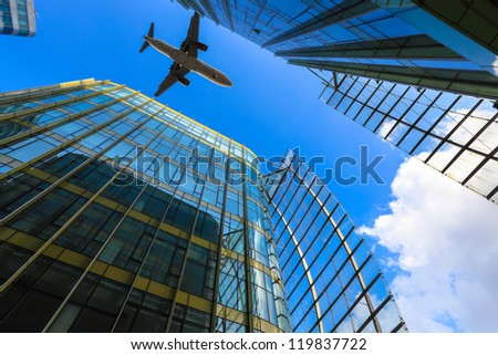 airliner and modern glass building against a blue sky
