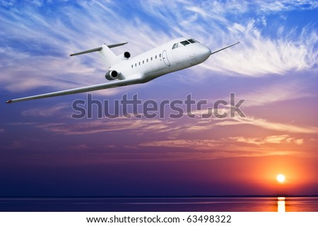 Airliner flying above tropical sea at sunset
