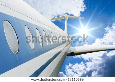 Airliner flying in high cloudy sky with bright sun