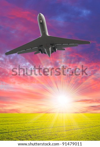 Airliner over the spring meadows against beautiful sunset. Travel concept - last minute metaphor.