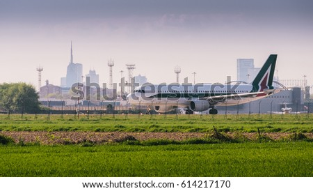 Airplaline at Milan, Italy's Linate airport with Milan's iconic skyline in the background