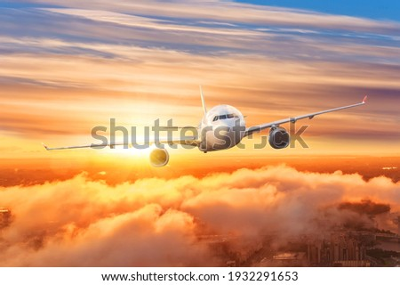 Airplane above the clouds in the sky at sunrise Foto stock ©