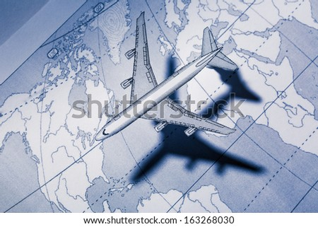 Airplane above the map in blue - stock photo