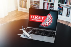 Airplane and flight cancellation. Flight cancelled. Pandemic of coronavirus. Coronavirus 2019 COVID-19 theme. Coronavirus with flight cancelled wallpaper on computer. Scale model airplane by computer.